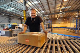 Man placing box on shipping conveyor belt