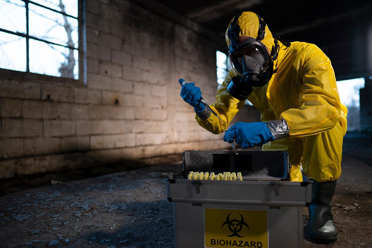 Man in hazmat suit with biohazard material