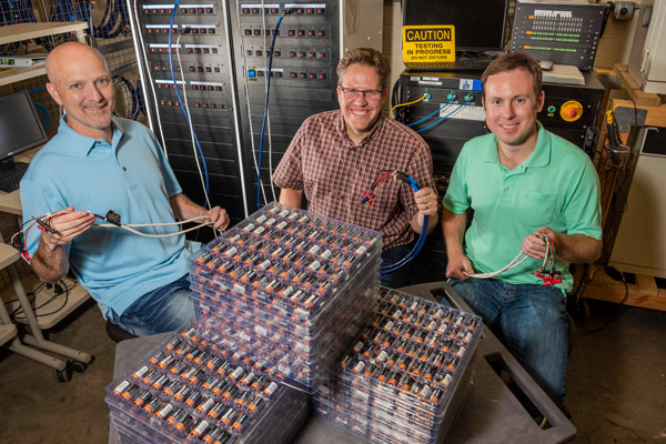 AMPS cofounders and Sandia engineer work on flat of batteries