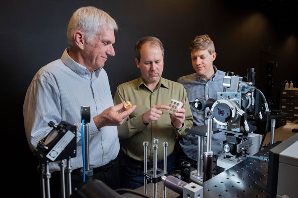 scientists evaluate metal sample with tabletop laser system