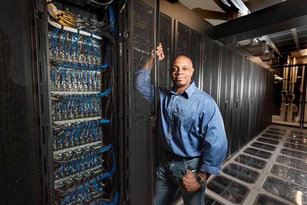 Warren Davis stands in front of large computer panel