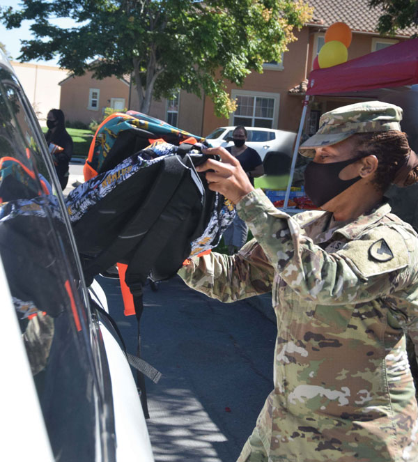 officer hands backpack to family at drive-up donation event