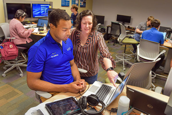 Tommie talks with intern in computer lab