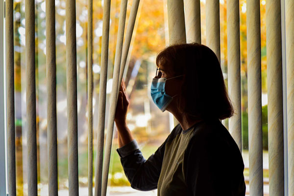 person in mask looks out window