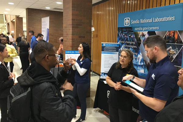 Signers, speakers and interpreters engaged with culturally deaf students at a career fair