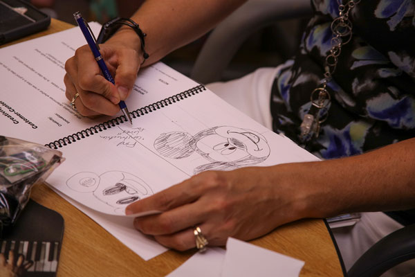 employee takes notes and sketches in notebook