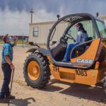 instructor stands by as student operates forklift