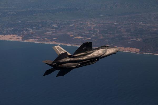 F-35A Lightning II jet fighter in flight over coastline