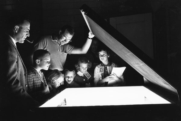 family day visitors in a dark room peer into a lit copy machine