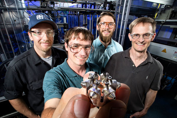 researchers holding up a ducted fuel injection module