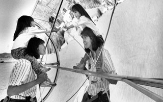 child sits on mom's shoulders as they look at their reflection in a parabolic trough
