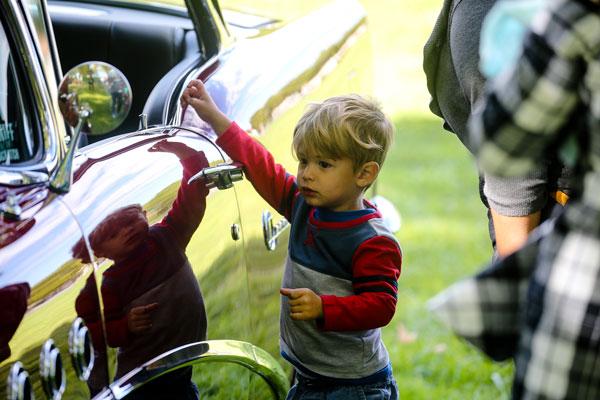 child looks at classic car