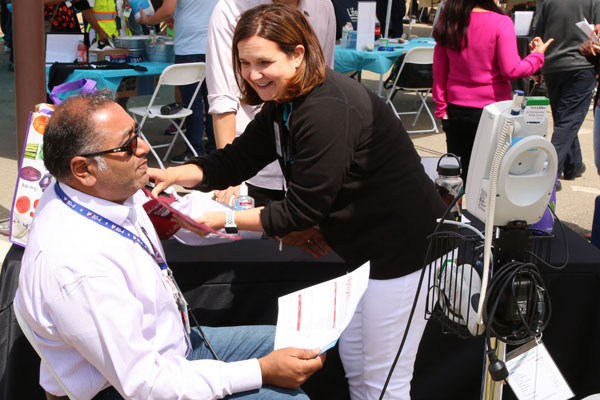 medical staff checks employee's blood pressure at booth