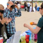 participants wear dark goggles and try to drop oranges in cups