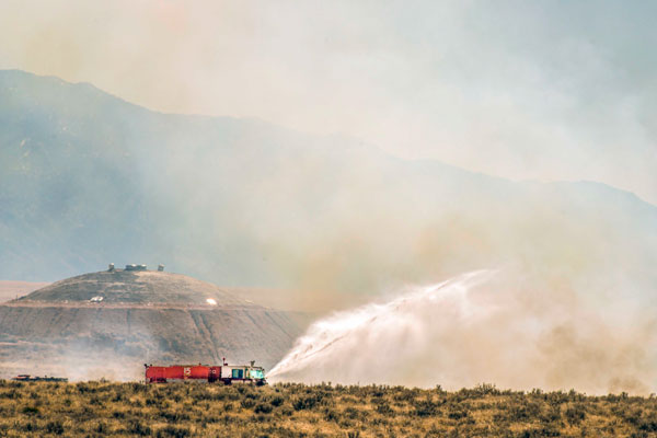 firetruck spraying water on brush fire in remote area of Sandia property