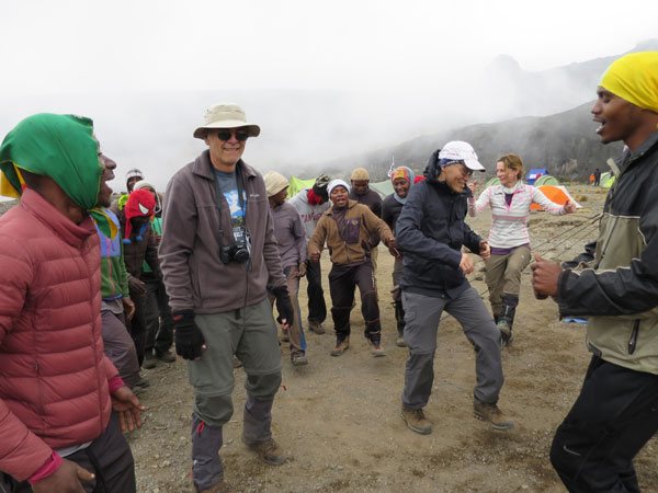 team dances with their guides at base camp