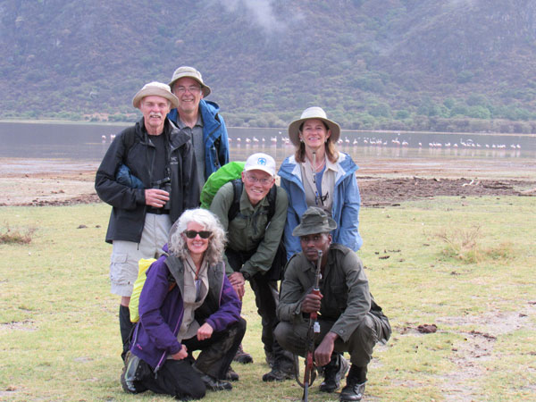 hiking group with guide on savanna with flamingos behind