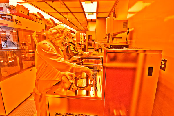 technicians in full protective suits work in lab under glow of orange lights
