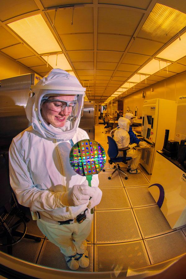 microelectronics technician in HAZMAT suit studies a wafer
