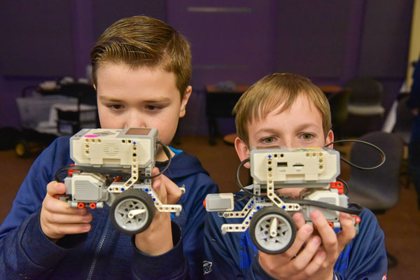 students inspect robot vehicle