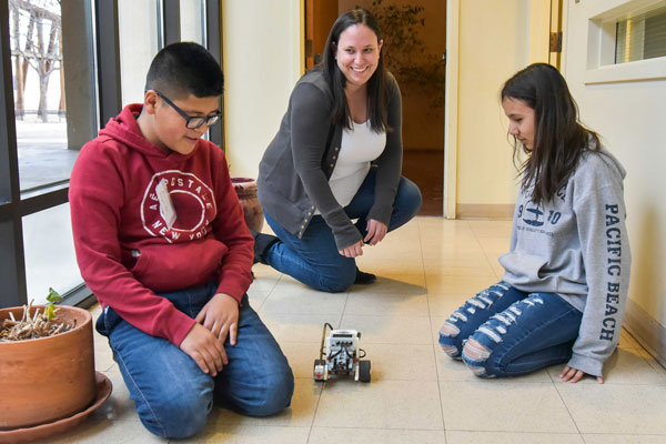 students and volunteer test robot vehicle