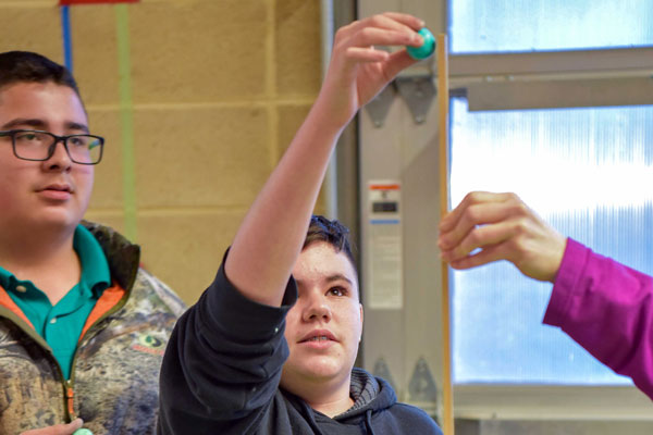 students and volunteer conduct gravity experiment