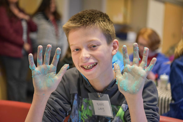 student shows hands covered in gooey blue substance