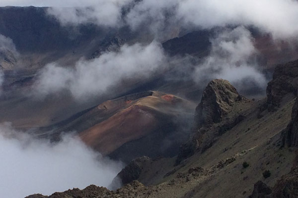 view of mountain tops shrouded in clouds