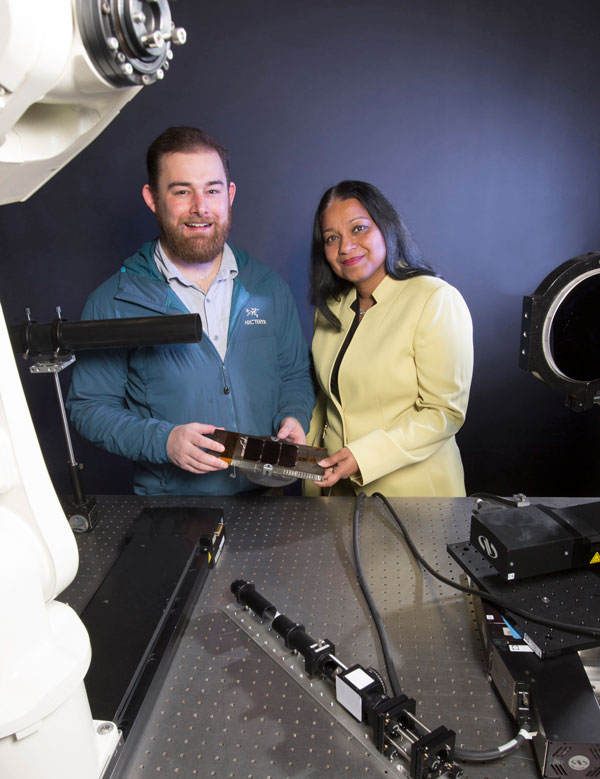 Sandia scientist and small business CEO hold titanium part in lab