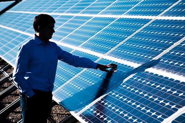 engineer examines solar panel