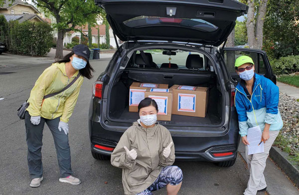 volunteers pack vehicle with PPE donations