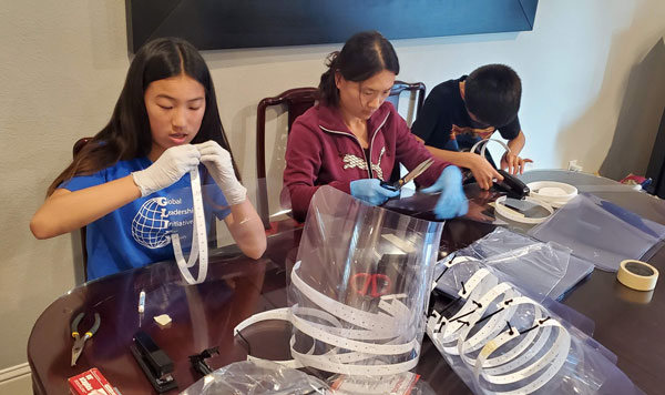 Helena Jin and her children assemble face shields