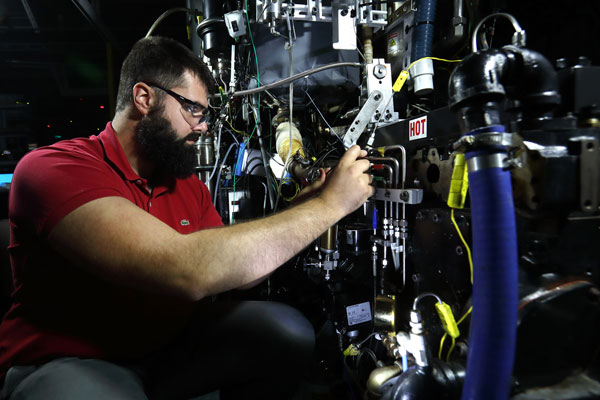 Researcher adjusts engine part in lab
