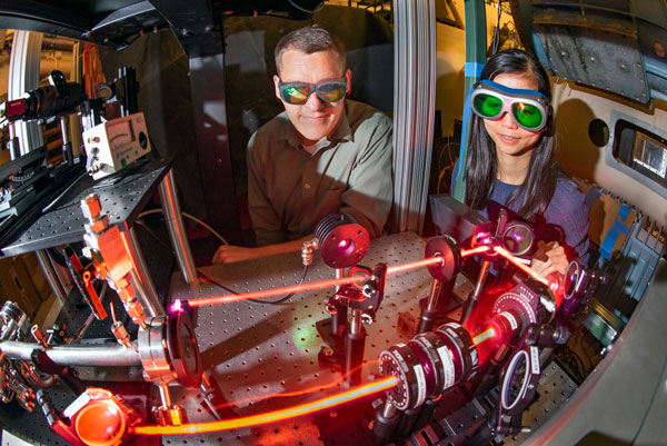 scientists observe laser recording measurements in wind tunnel