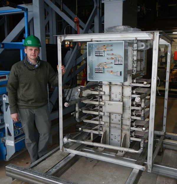 engineer stands next to particle-supercritical CO2 heat exchanger