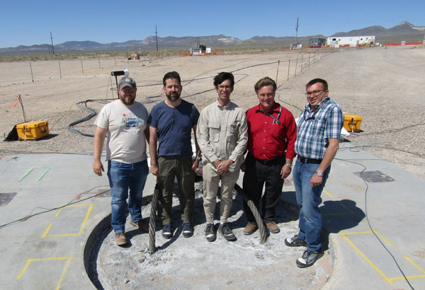 sandia researchers stand on filled borehole