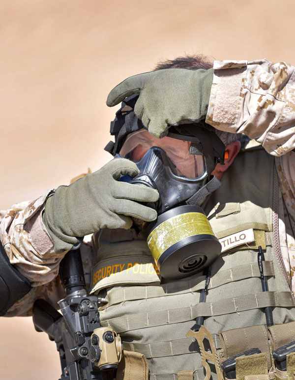security police officer puts on gas mask