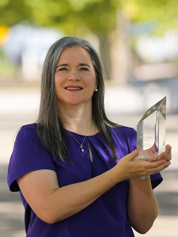Anne Grillet holding her SWE award