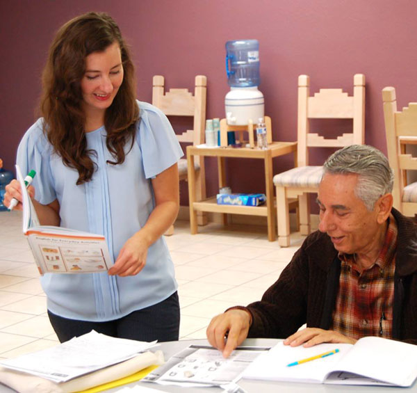volunteer works with man on reading assignment