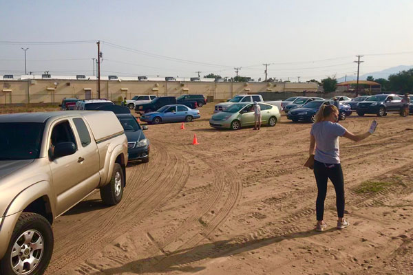 volunteer directs cars at food donation pick-up
