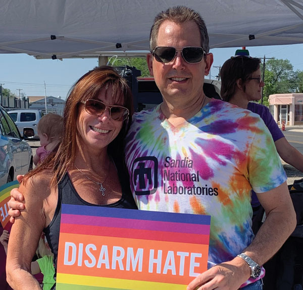 Mark and his wife hold disarm hate sign at PRIDE parade