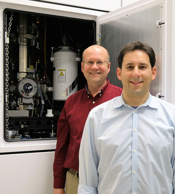 Sandia materials scientists Doug Medlin (left) and Josh Sugar (right) pose in front of Sandia's new transmission electron microscope.