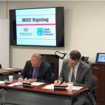 UNM's Craig White and Sandia's Scott Aeilts sign a memorandum of understanding