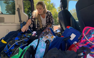 volunteer loads SUV with backpacks to donate