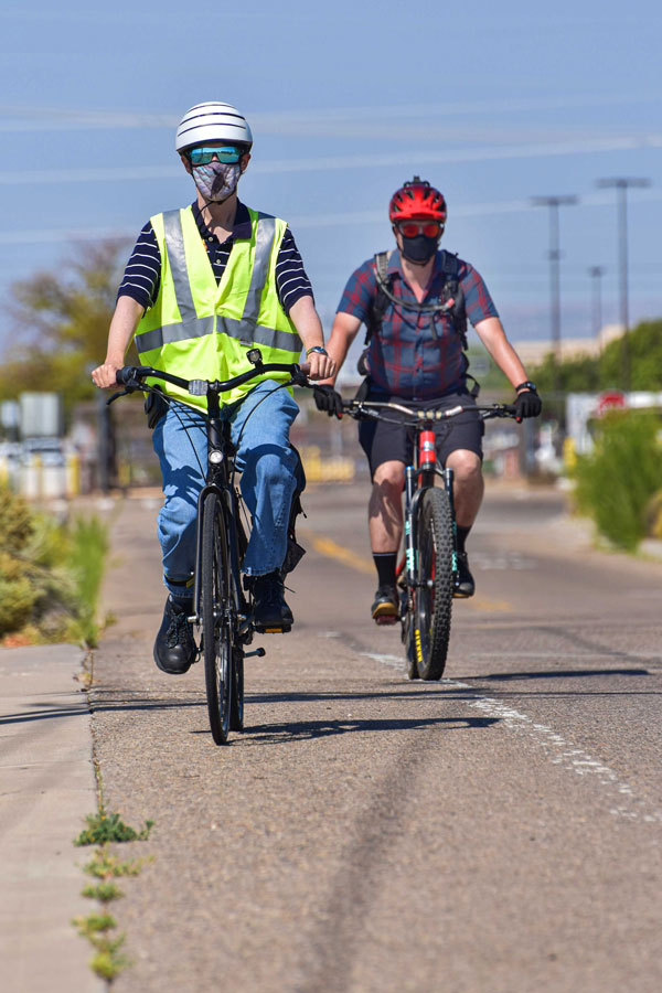 cyclists wearing face masks ride bikes on-site