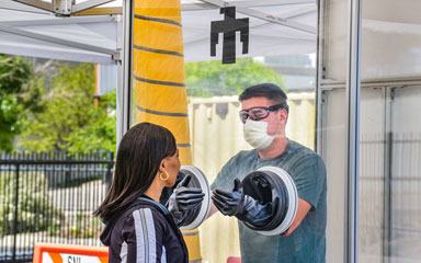 medical worker tests patient from inside portable testing booth