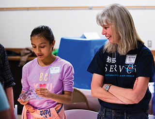 """Sandia President and Labs Director Jill Hruby, in photo above, engages with a local student during a """"What is Fire?"""" demonstration at Sandia's first STEM Mentoring Café, a DOE outreach program to engage middle school girls."""