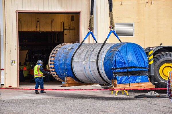 giant steel canister being loaded into warehouse