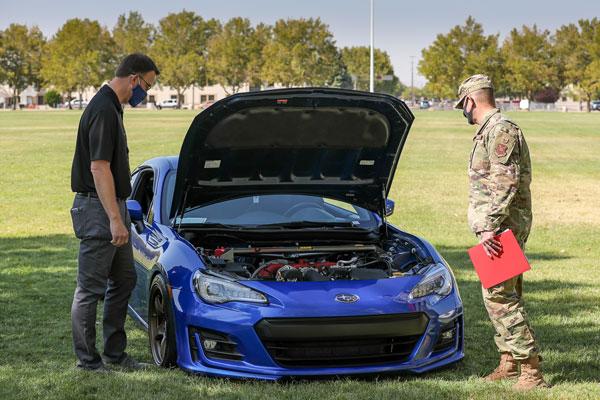 judges inspect car at car show
