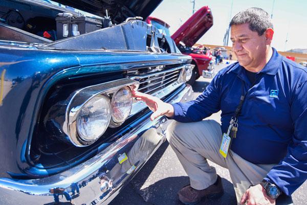 man examines front bumper of classic car